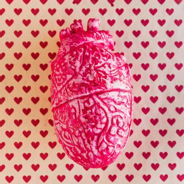 Cuore umano in ceramica rossa sul tavolo con motivo a cuore Foto Gratuite