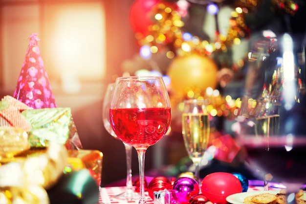 Red champagne glasses on table with gift boxes. merry christmas, happy new year celebratio Premium Photo