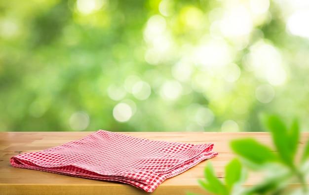 木の上の赤いチェックのテーブルクロスと木のぼけ緑のボケ味 Premium写真
