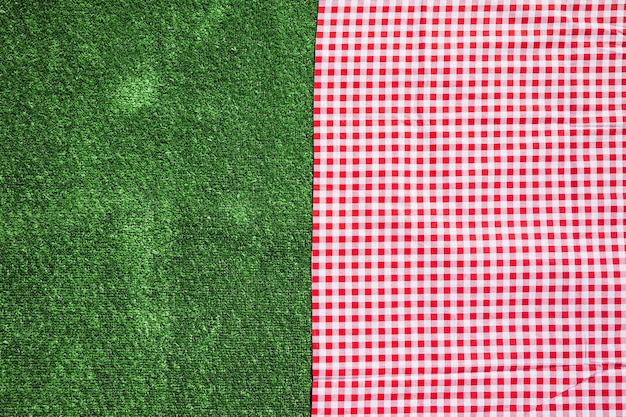 Red checkered table cloth and green turf background Free Photo