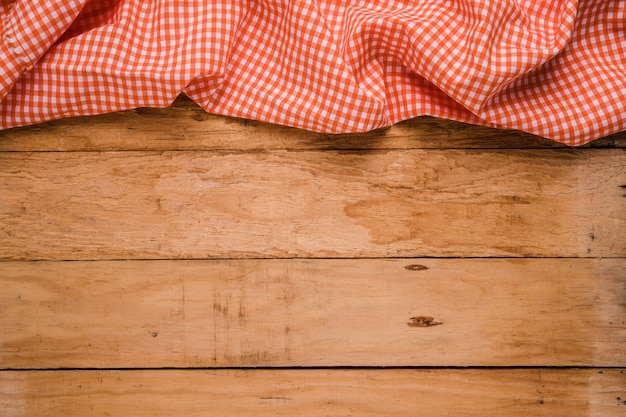 Red checkered table cloth at the top of old wooden worktop Free Photo