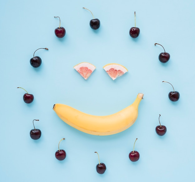 Red cherries arranged in circular frame with smiley face made with banana and grapefruit on blue background Free Photo