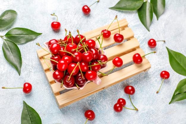 Красная вишня в тарелку на сером столе Бесплатные Фотографии