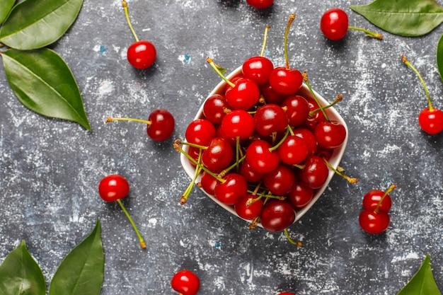 灰色のテーブルの上の皿のボウルに赤いサクランボ 無料写真