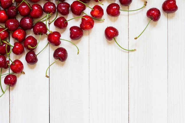 Red cherries on white wood Free Photo