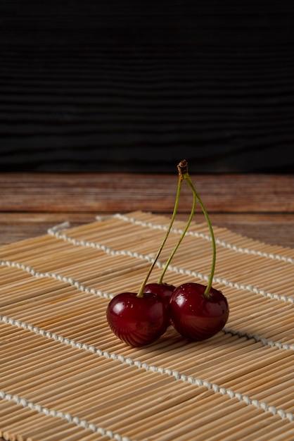 素朴なマットに緑の茎を持つ赤いサクランボ 無料写真