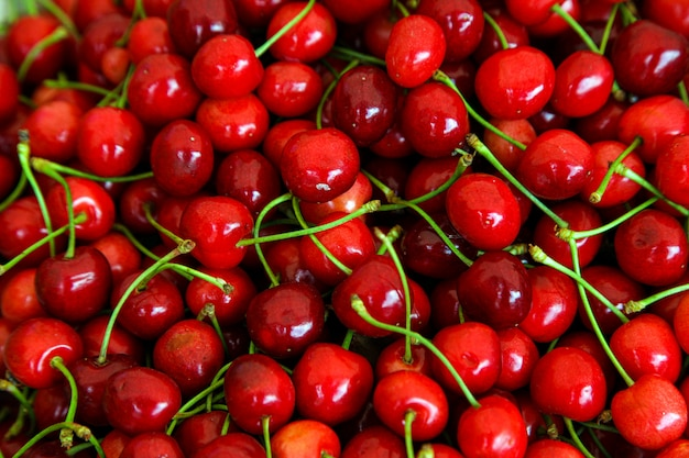 Red cherries with green stems, top view Free Photo
