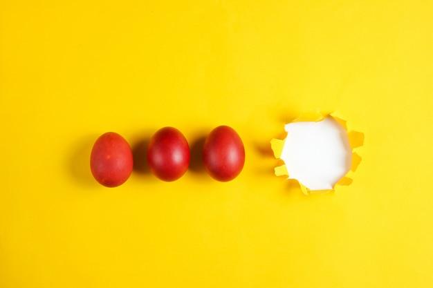 破れた穴のある黄色の紙のテーブルに赤い鶏の卵 Premium写真