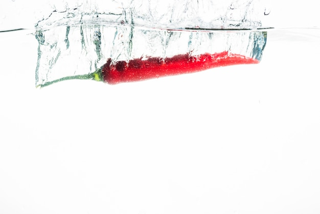 Red chili falling into water against white background Free Photo