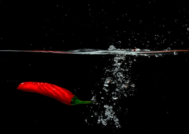 Red chili falling with bubbles into water against black background Free Photo