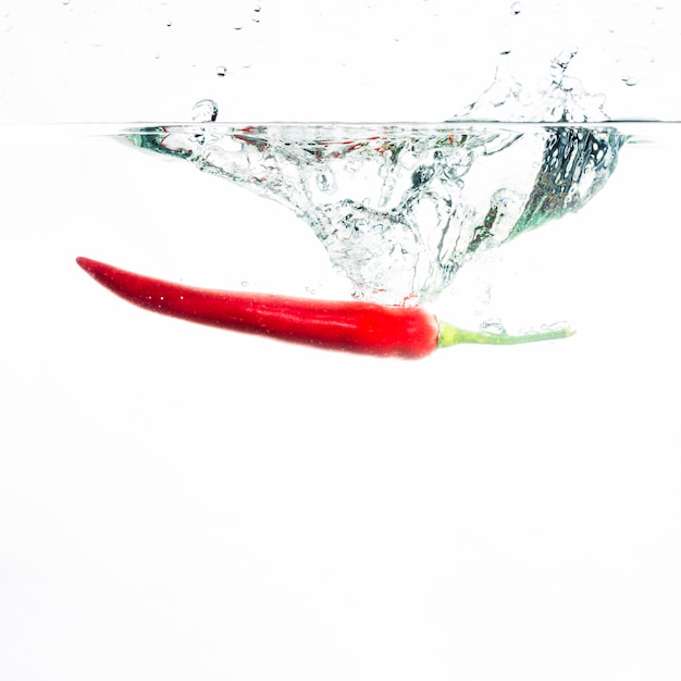 Red chili falls deeply under water with a big splash Free Photo
