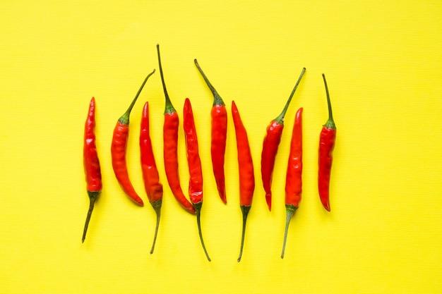 Red chili pepper pods on bright yellow background Premium Photo