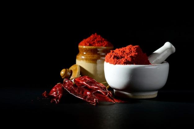 Порошок красного перца чили в пестике с ступкой и глиняный горшок с красным перцем чили на черной поверхности Premium Фотографии