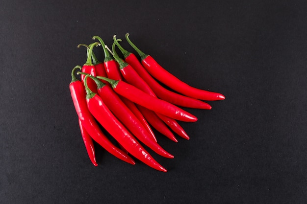 Red chili peppers on black surface Free Photo
