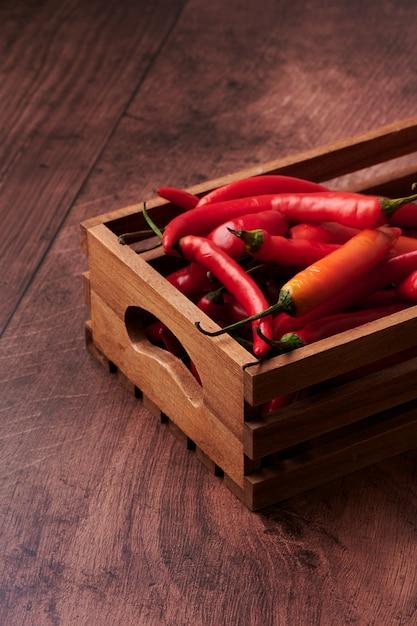 木製の表面に置くボックスに赤唐辛子 無料写真