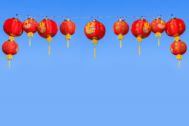Red chinese paper lanterns against a blue sky Premium Photo