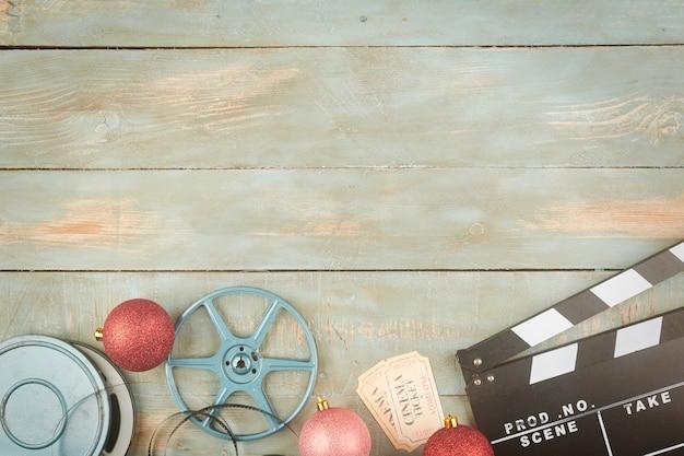 Красные новогодние шары и объекты кино на деревянном фоне Premium Фотографии