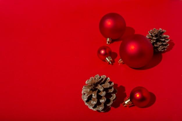 빨간색 크리스마스 볼과 빨간색 테이블에 소나무 콘 무료 사진