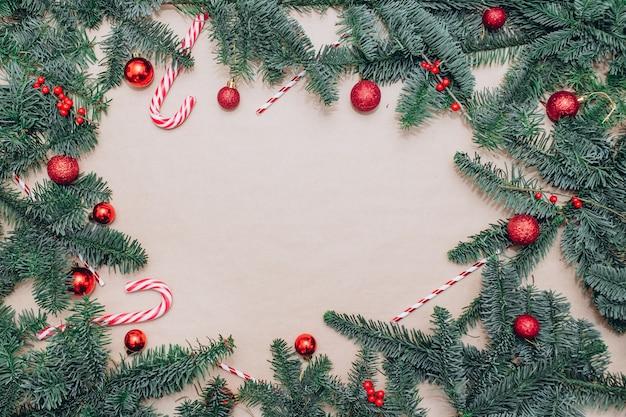 テーブルの上にある赤いクリスマスボール、モミの枝、球根とガーランド Premium写真