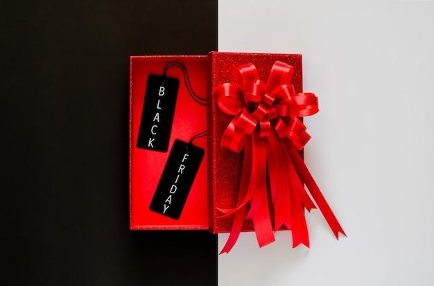 Красная рождественская коробка с красной лентой-бантом и черным ценником на черно-белом Premium Фотографии