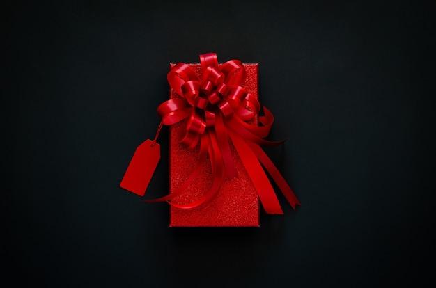 Красная новогодняя коробка с красной лентой и ценником на черном Premium Фотографии