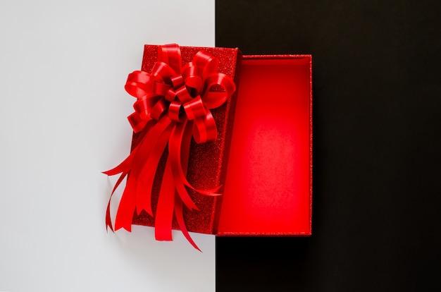 Красная рождественская коробка с красной лентой банта на черно-белом. Premium Фотографии