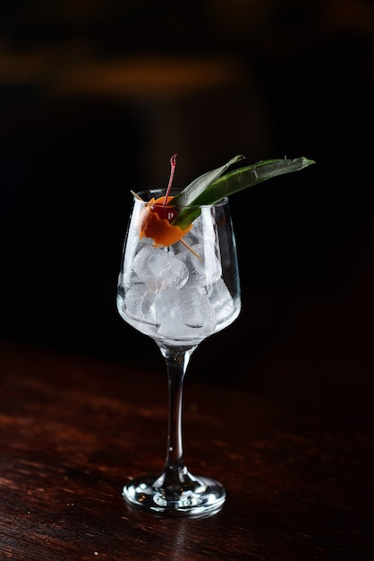 Red cocktail with ice and cherry in a transparent glass. liquid pouring into a glass Premium Photo