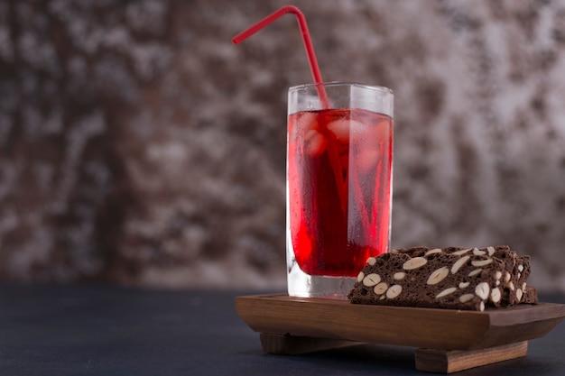 Красный коктейль с кубиками льда в стакане с кусочком торта в сторону Бесплатные Фотографии