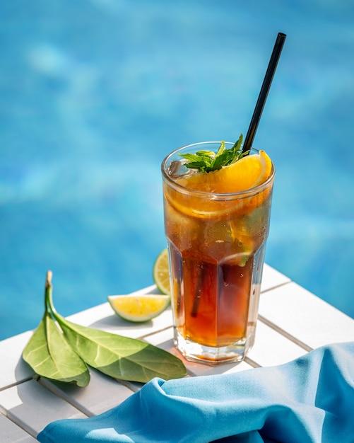 Cocktail rosso con limone, fettine di arancia ed erbe hreen a bordo piscina. Foto Gratuite
