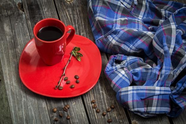 美しい木製の背景、飲料、散乱のコーヒー豆のプレートに赤いコーヒーカップ 無料写真
