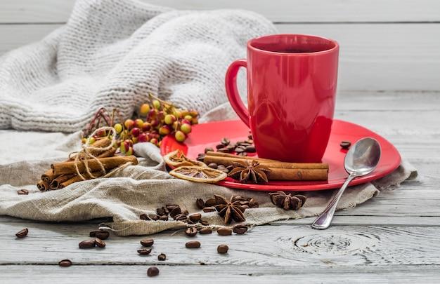 プレート、木製のテーブル、飲料の赤いコーヒーカップ。 無料写真