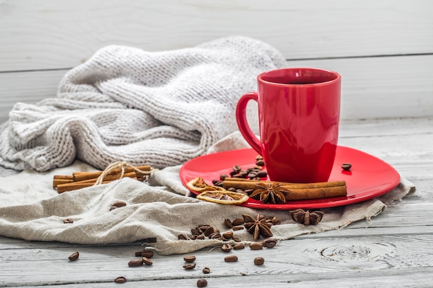 Red coffee cup on a plate, wooden wall, beverage Free Photo
