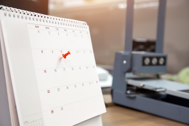 A red color pin on calendar, concept for events planner. Premium Photo