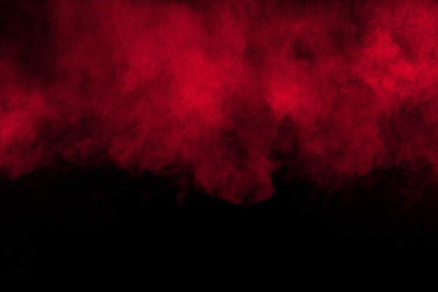 Red color powder explosion on black background.red dust particles splashing. Premium Photo