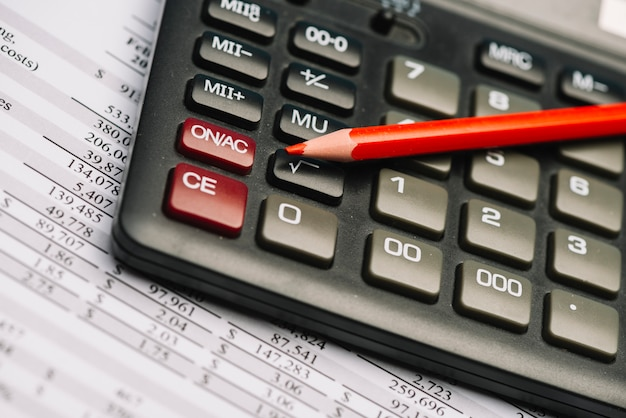 Red colored pencil on calculator over the financial report Free Photo
