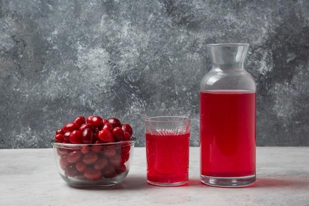 Красные ягоды кизила в стакане с соком в сторону. Бесплатные Фотографии