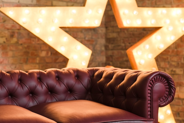 Red cozy sofa in front of glowing star against brick wall Free Photo