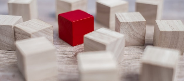 Red cube block different from crowd of wood blocks. Premium Photo