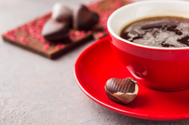 Red cup of coffee and chocolate candy in a heart shape over gray background close up. valentine's day concept. Premium Photo