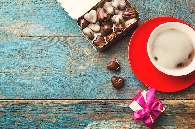 Red cup of coffee and gift box over blue wooden table. top view. valentine's day concept. Premium Photo