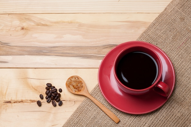 Red cup coffee and sugar in spoon on burlap coffee bean on wood board Premium Photo