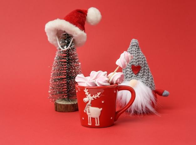 Красная чашка с горячим шоколадом и зефиром и миниатюрная елка в шапке санта-клауса на красном фоне Premium Фотографии