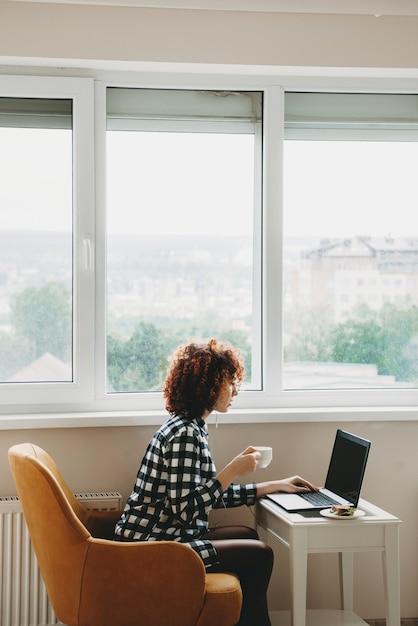 窓の近くのコンピューターでリモートで作業している赤い縮れ毛の白人ビジネスウーマンはお茶を飲み、サンドイッチを食べています Premium写真