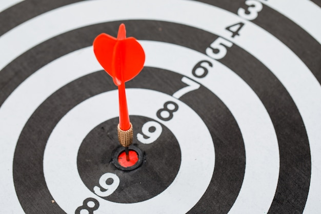 Red dart arrow hitting in center of dartboard Free Photo