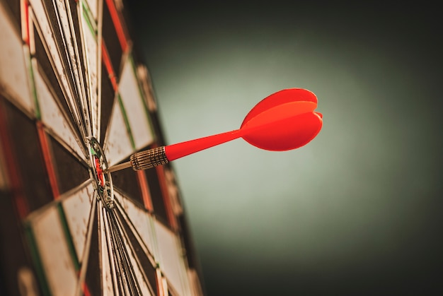 Red dart in the bulls eye center of a target Premium Photo