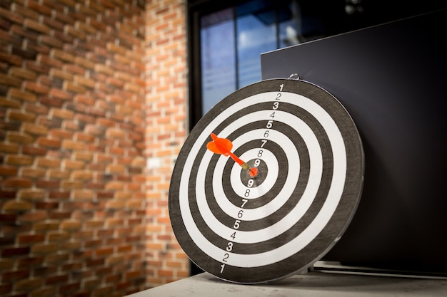 Red dart target arrow hitting on bullseye with, target marketing and business success Premium Photo