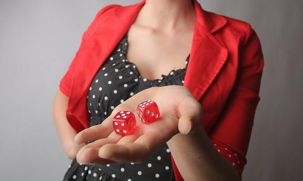 Dadi rossi nelle mani di una donna con una giacca rossa Foto Gratuite