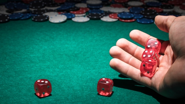 Red dice on human hand in casino Free Photo