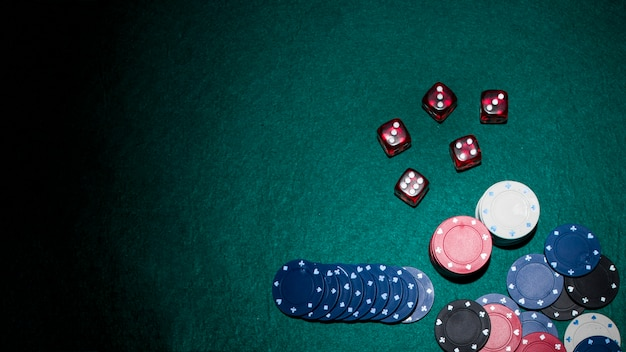 Red dices and casino chips on green poker table Free Photo