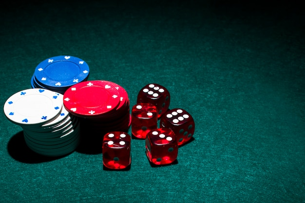 Red dices and casino chips stack on green poker table Free Photo